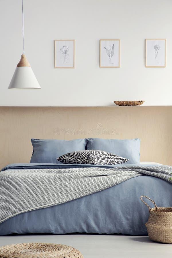 Lampe au-dessus de lit bleu avec des oreillers dans l'intérieur de chambre à coucher de boho avec p image stock