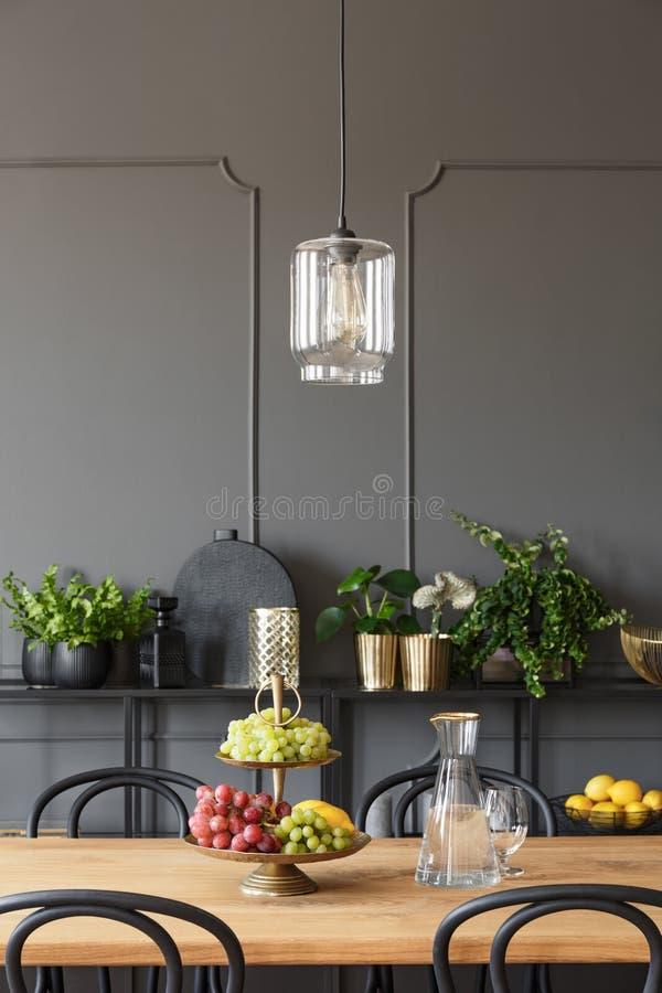 Lampe au-dessus de table en bois avec des fruits dans l'intérieur gris de salle à manger image libre de droits