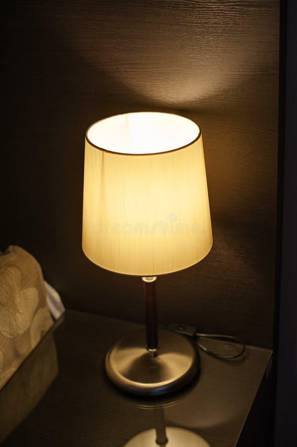 Lampe auf dem nightstand im Schlafzimmer nahe bei dem Bett stockfotos