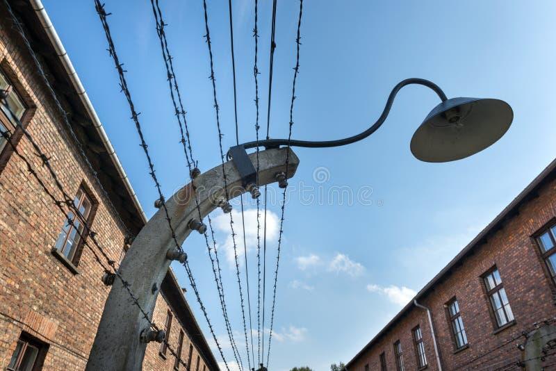 Lampe auf einem Stacheldraht schließt das Lager Auschwitz II-Birkenau in Brzezinka, Polen ein stockbild