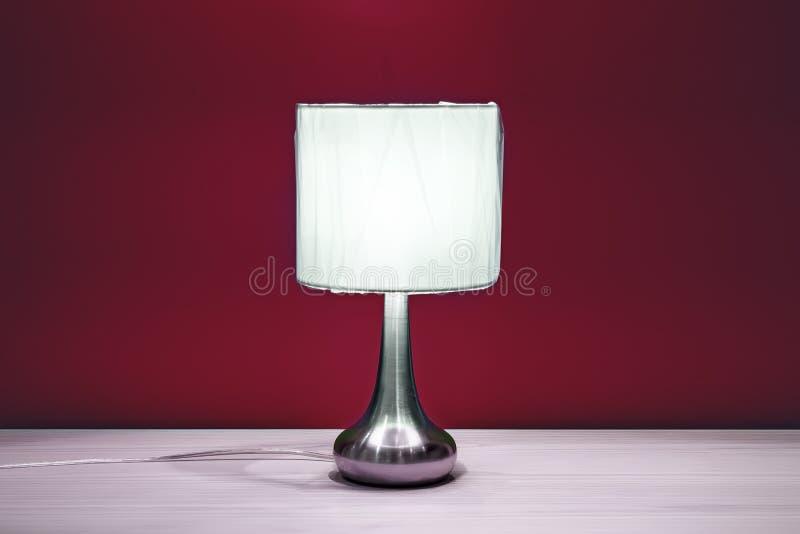 Lampe auf einer Nachttabelle nahe bei einem Bett stockfoto