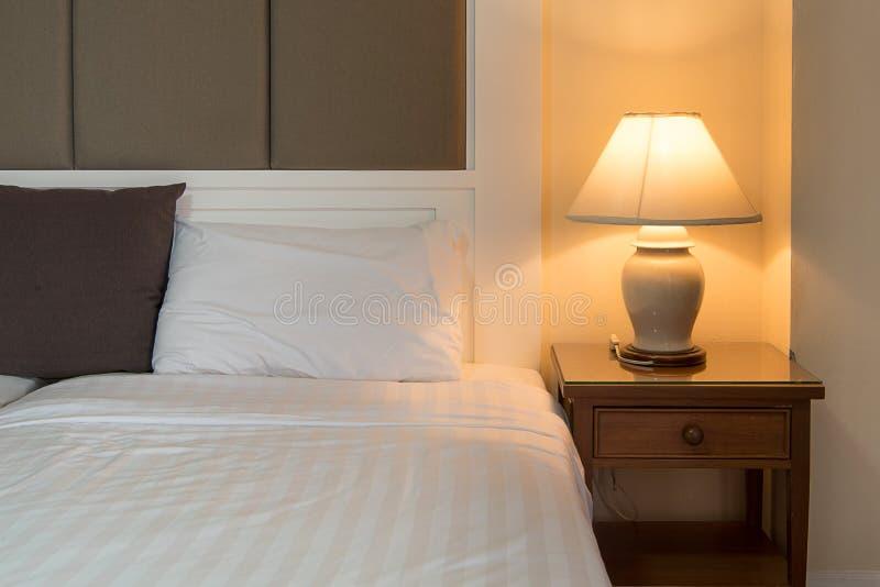 Lampe auf einer Nachttabelle nahe bei klassischem Bett stockbild