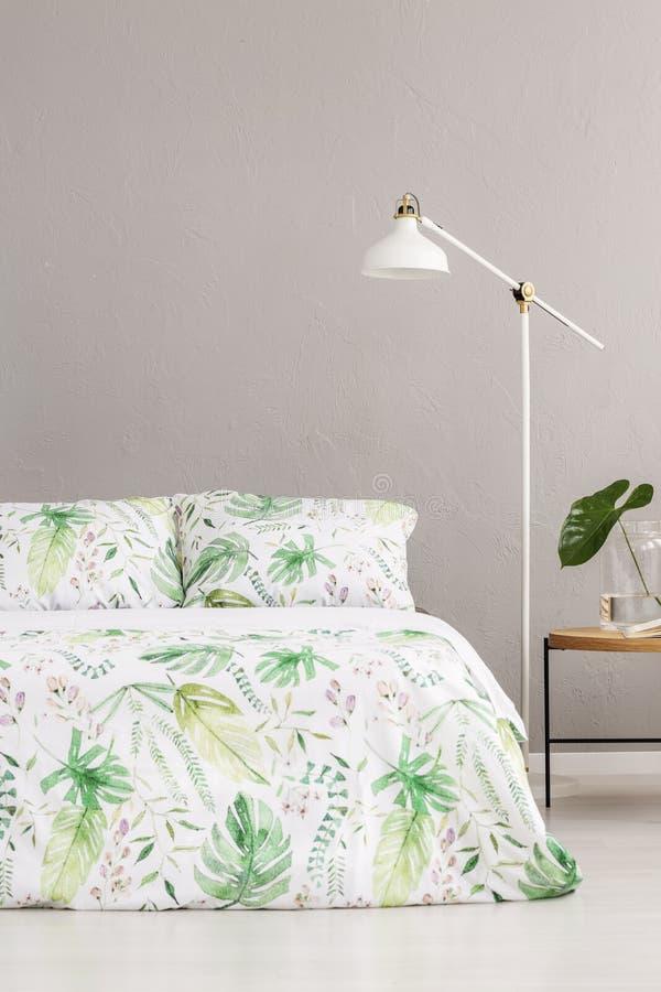 Lampe blanche entre le nightstand en bois et le lit grand avec la literie florale, vraie photo avec l'espace de copie sur le mur  photos stock