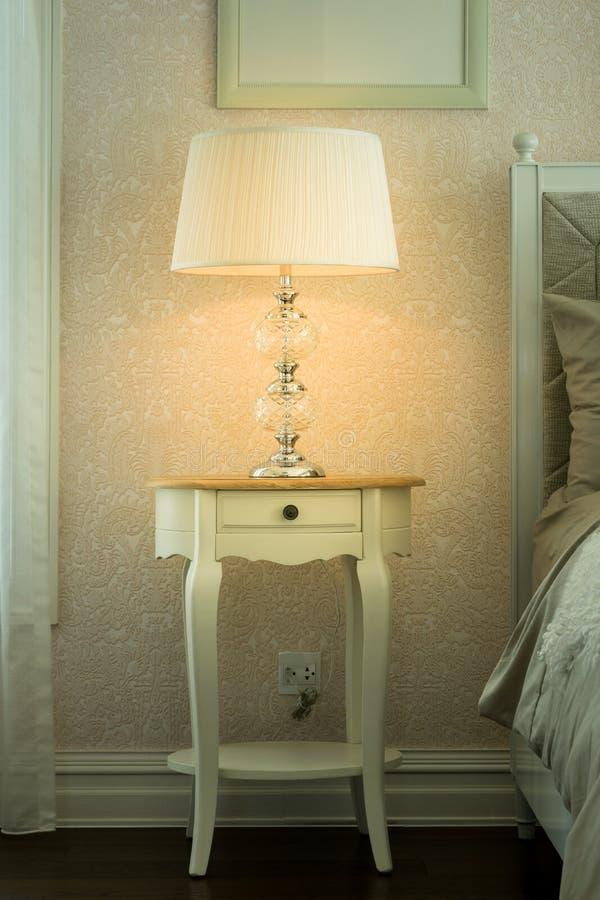 Lampe blanche sur la table en bois de chevet photo stock