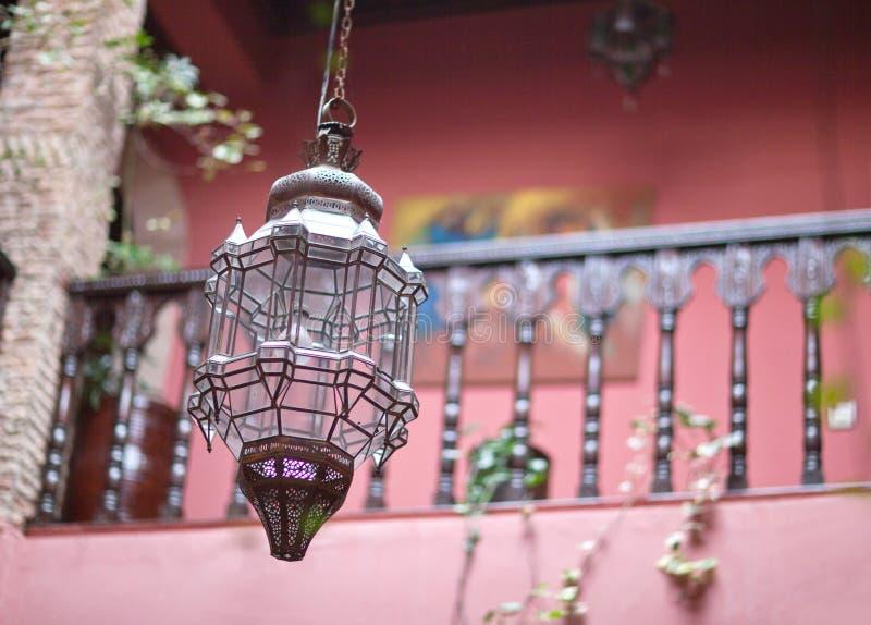 Lampe de cuivre en verre marocaine traditionnelle dans l'intérieur oriental de riad photographie stock libre de droits