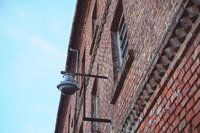 Lampe de design industriel sur le bâtiment rouge industriel abandonné de façade de mur de briques, diagonal de dessous la vue photographie stock