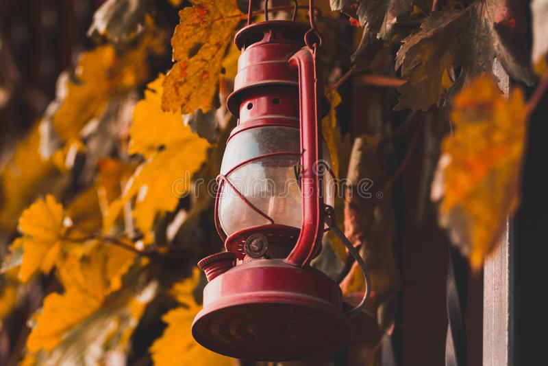 Lampe de kérosène rouge sur la barrière avec des feuilles photographie stock