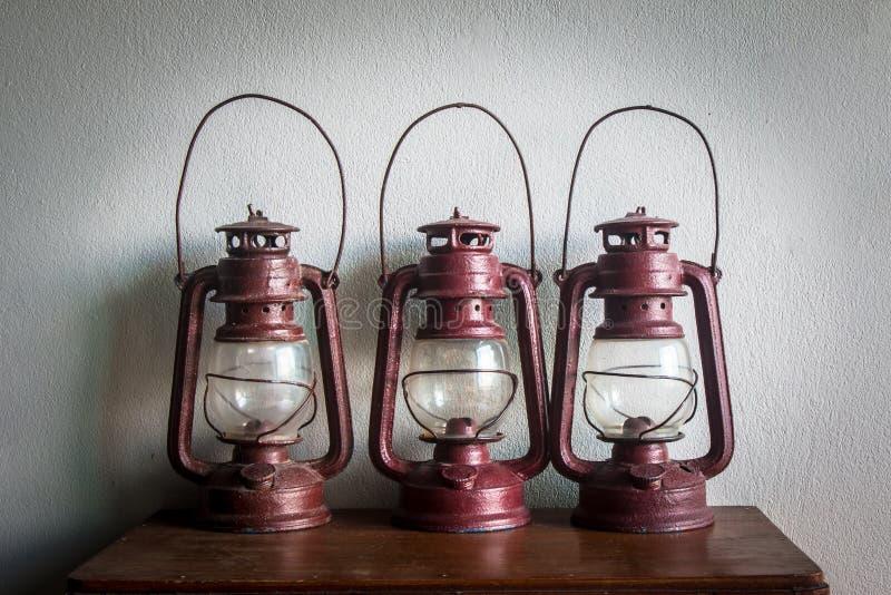 Lampe de kérosène de trois vintages sur la table en bois images stock