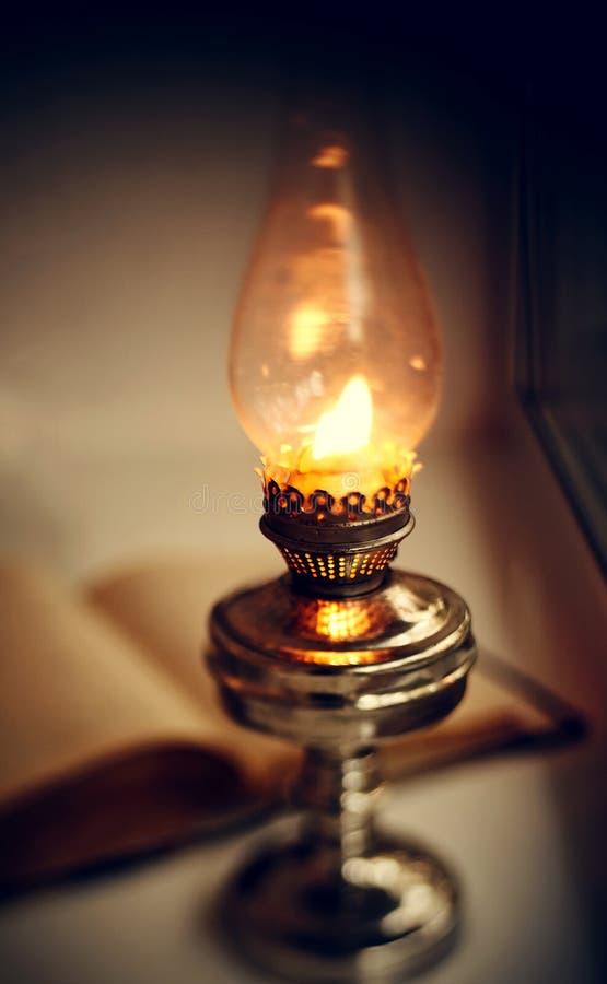 Lampe de k?ros?ne de cru et vieux livre ouvert photos libres de droits