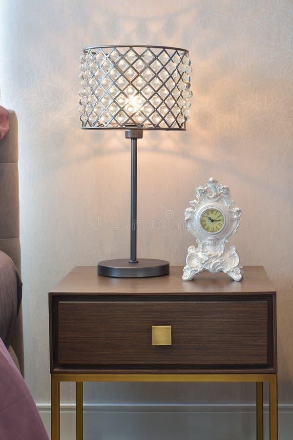 Lampe de lecture en cristal et horloge classique sur la table de chevet photos libres de droits