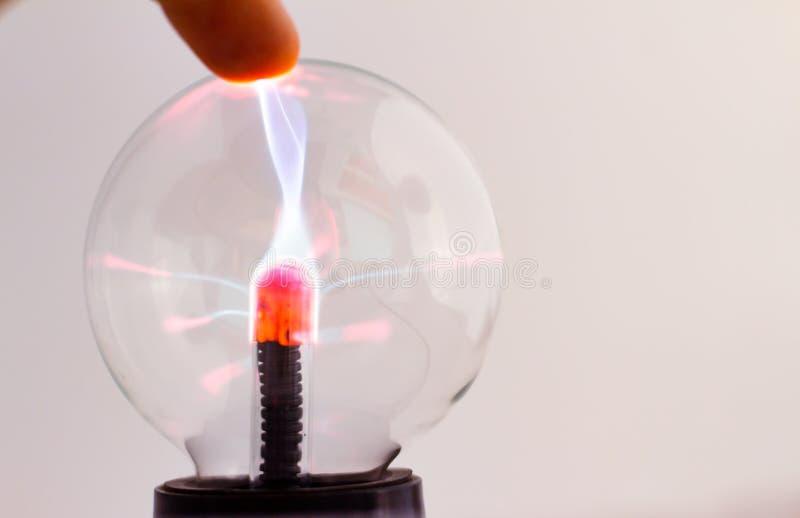 Lampe de plasma sur le fond neutre Doigts d'un homme attirant l'écoulement électrique lumineux Boule de cristal avec l'électricit photo stock