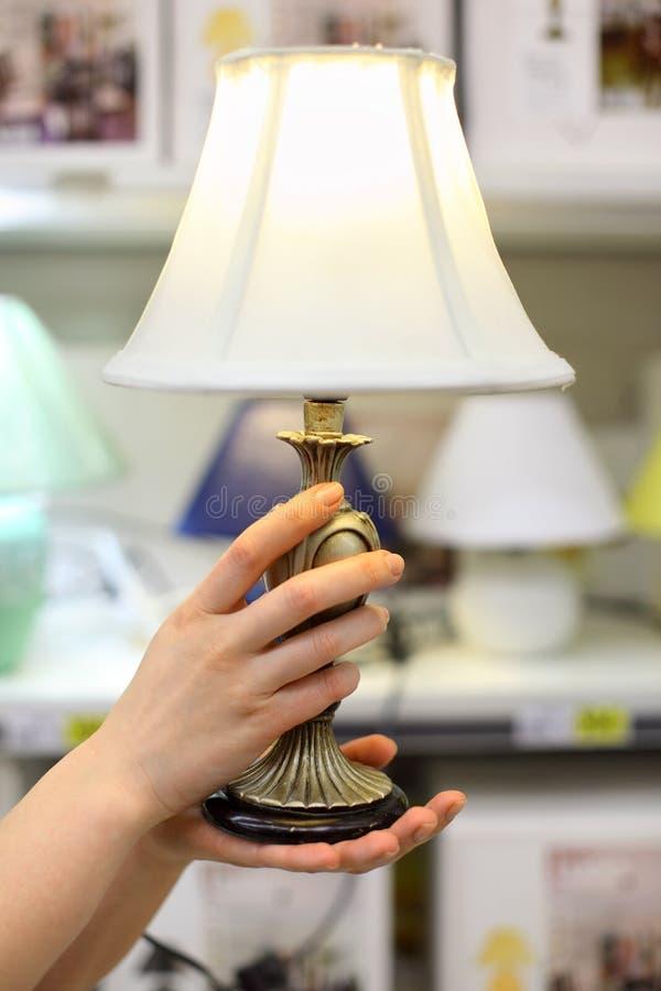 Lampe de table de prise de mains de femme dans le système photographie stock libre de droits