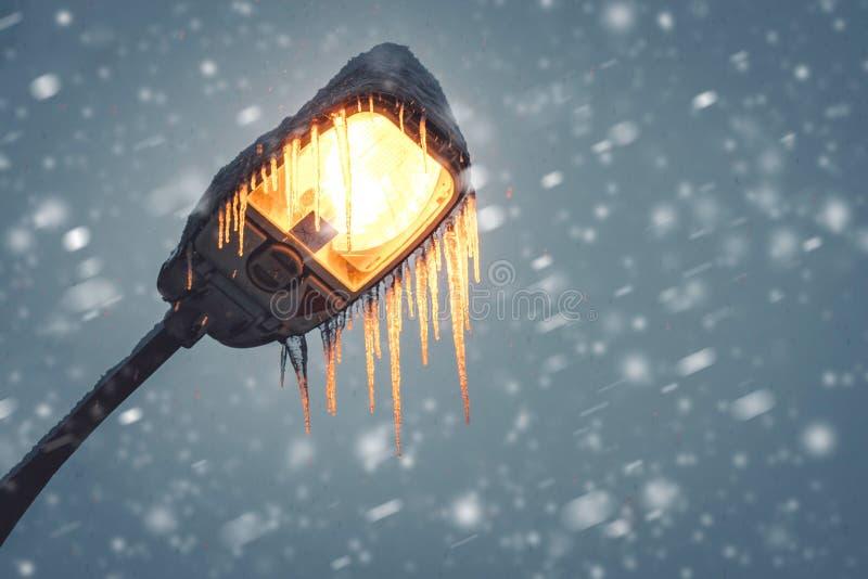 Lampe de ville dans l'horaire d'hiver par le temps orageux neigeux lourd image stock