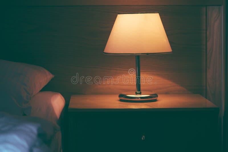 Lampe de vintage sur la table de nuit dans la chambre d'hôtel image libre de droits