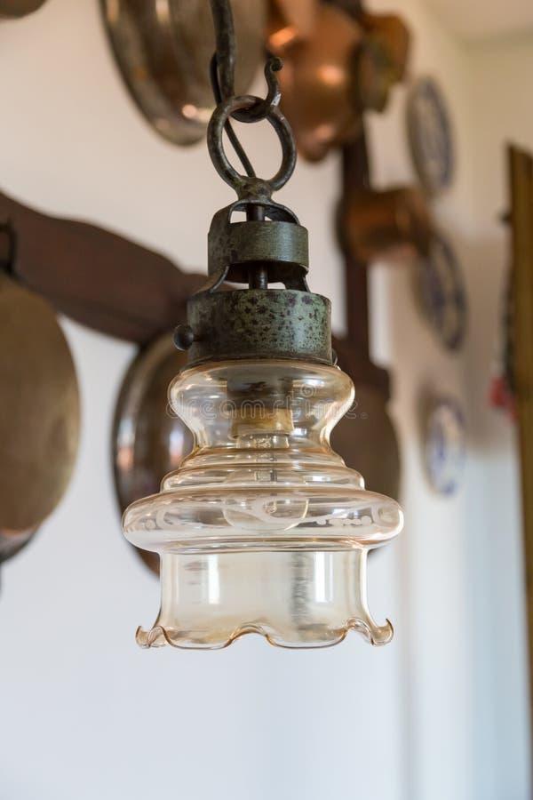 Lampe de vintage sur le mur de fond avec les ustensiles de cuivre antiques photo stock