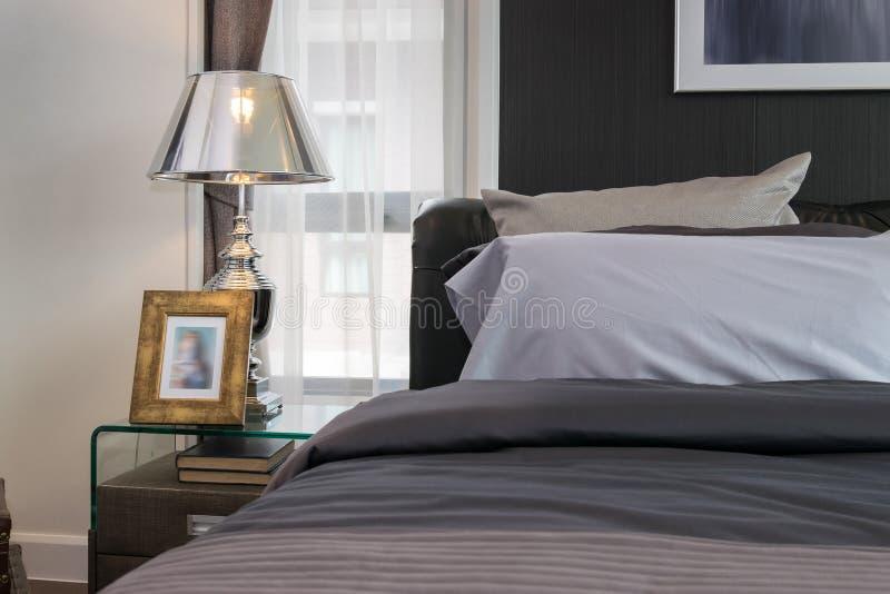 Lampe et cadre de tableau sur la table de chevet dans la chambre à coucher photos stock