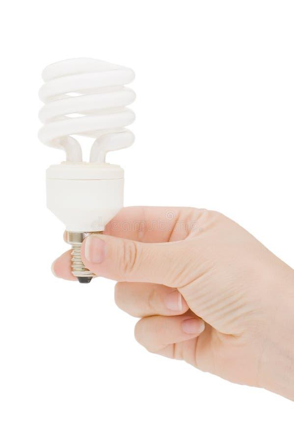 Lampe fluorescente spirale-formée par fixation de main photographie stock libre de droits