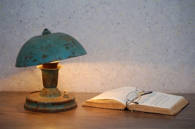 Lampe, Gläser und offenes Buch stockfoto