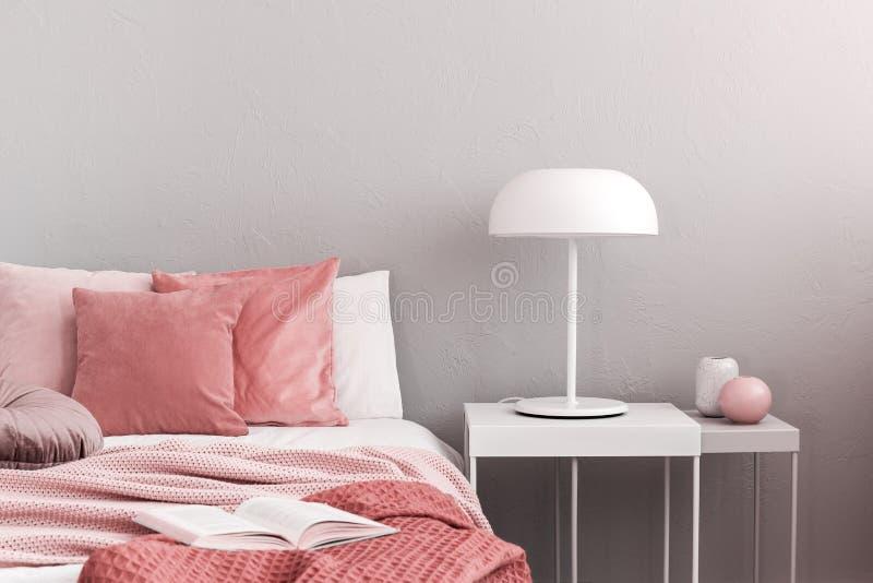 Lampe industrielle blanche sur une simple table de nuit à côté d'un lit douillet avec literie rose images libres de droits