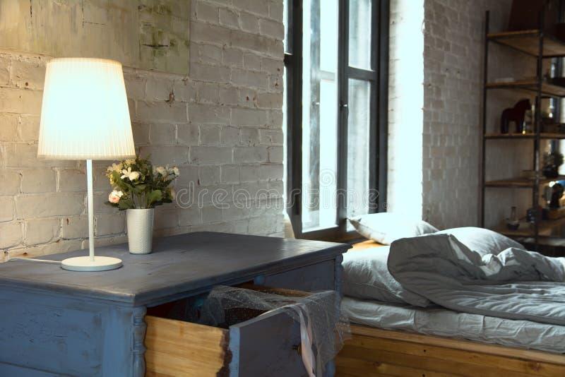 Lampe mit hölzernen Kommode für Leinen und ein Bett mit Kissen am Fenster stockfotos