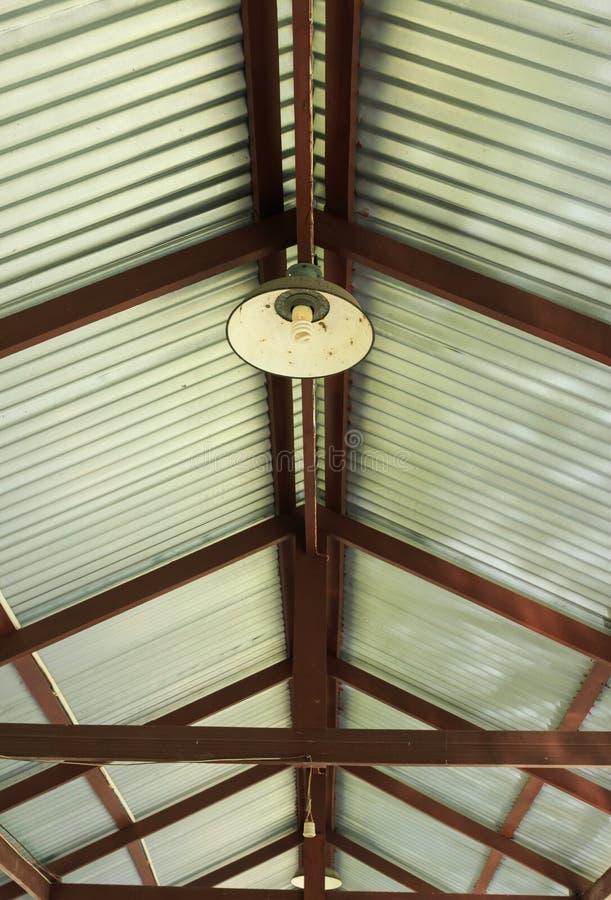 Lampe nette en métal accrochant sous le toit de zinc photos libres de droits
