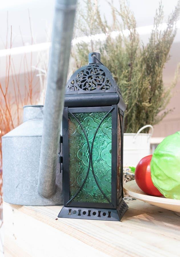 Lampe noire avec un verre vert placé sur une table en bois images libres de droits