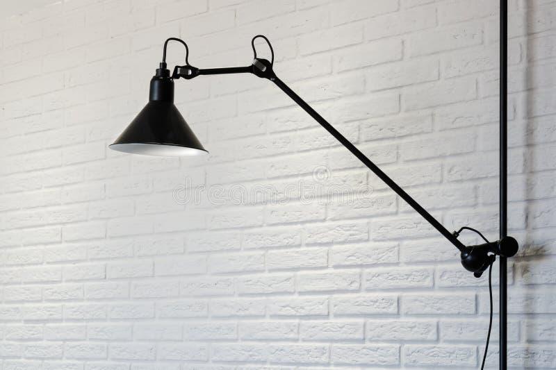 Lampe noire sur un fond blanc de brique Fragment de l'intérieur photos stock