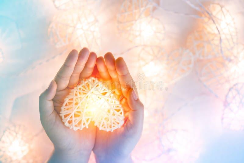 Lampe orange en pastel molle dans les paniers en bambou dans la forme de coeur sur la main deux photographie stock