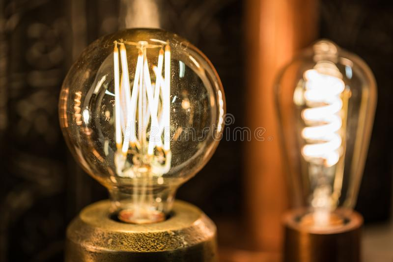 Lampe ronde stylisée de tungstène de cru rougeoyant dans la photo foncée et en gros plan avec le foyer sélectif et le DOF peu pro images stock