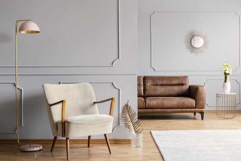 Lampe rose à côté de fauteuil dans l'intérieur gris d'appartement avec la feuille d'or et le tapis lumineux photos stock