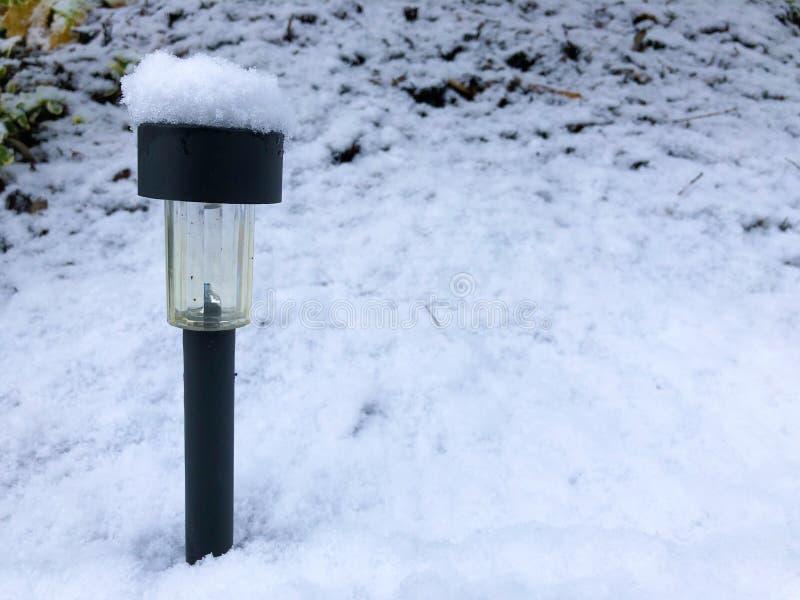 Lampe solaire d'energie de jardin moderne noir sous la neige photos libres de droits
