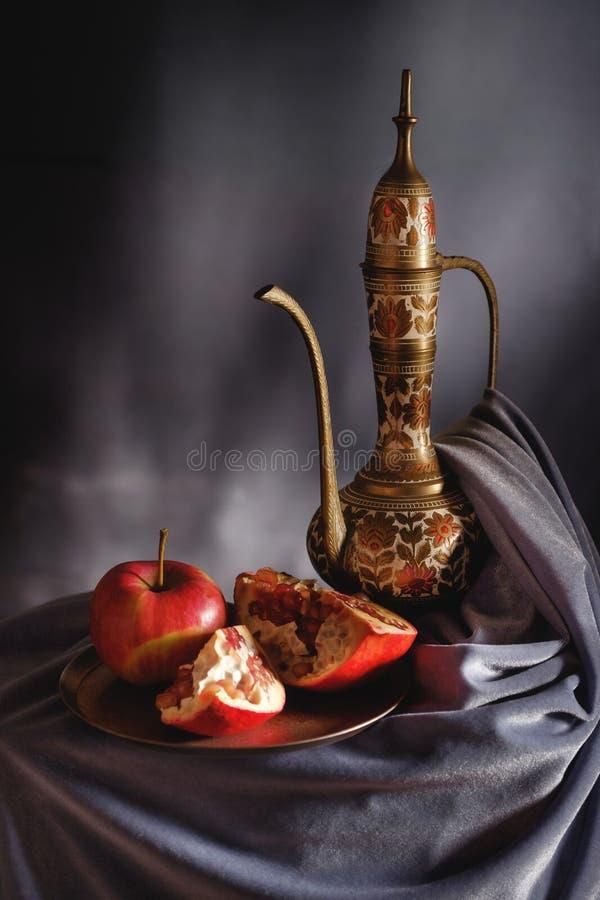 Lampe sous forme de cruche sur un fond gris avec des fruits photo libre de droits