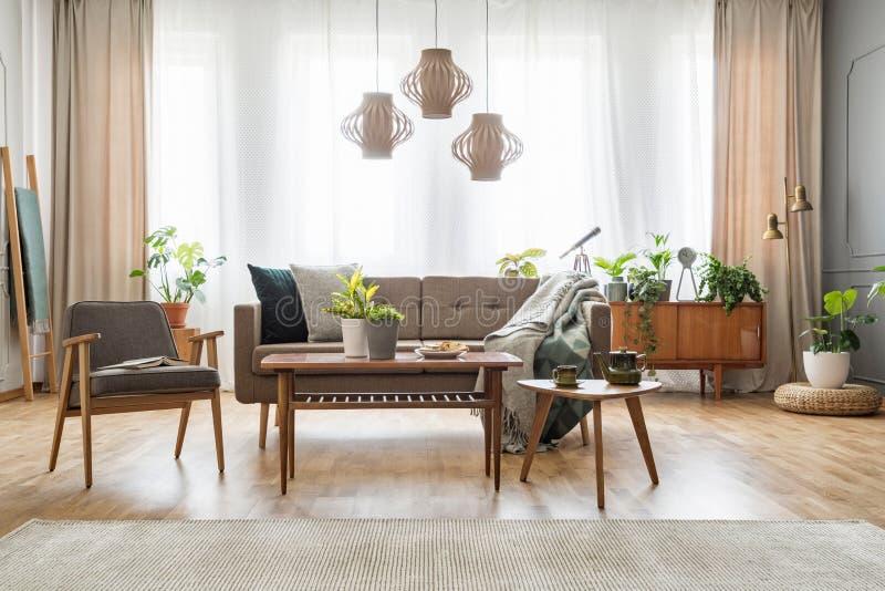 Lampen boven houten lijst met bloemen in helder woonkamerbinnenland met bank en leunstoel Echte foto stock foto's