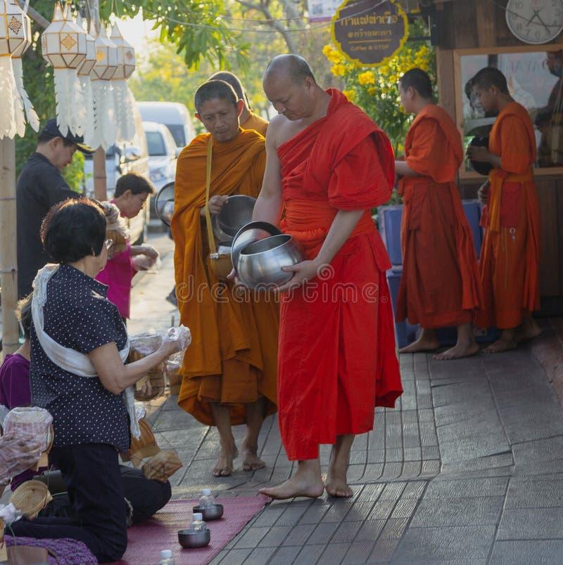 Lampeng, Tahiland - 2019-03-07 - linha de monges recebe presentes do alimento dos Worshippers ao longo da rua foto de stock royalty free