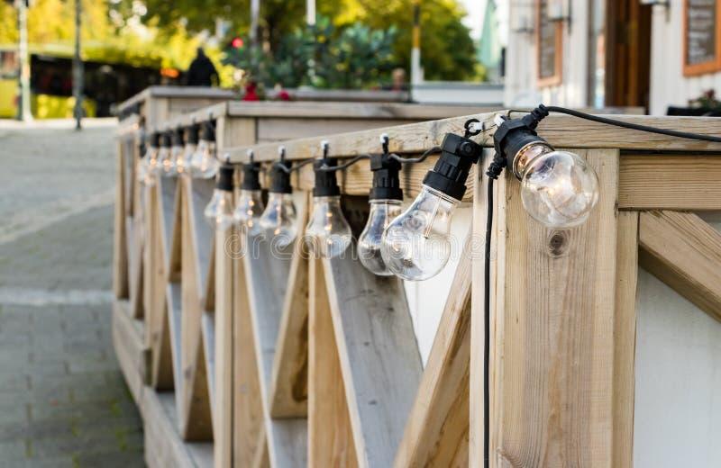 Lampes de câble d'edison d'ampoule avec le filament mené placé sur une balustrade en bois, dehors photo libre de droits