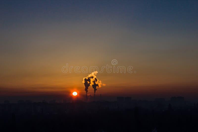 Lampglas och mörk rök över fabrik på solnedgången royaltyfri foto