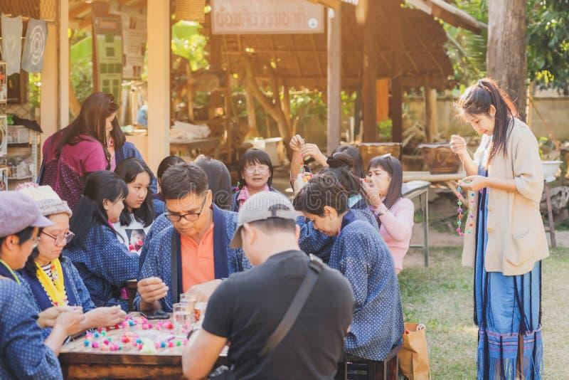 LAMPHUN THAILAND - DECEMBER 12 : Niet-geïdentificeerde Thaise vrouwelijke toeristen leren op 12 december 2019 een ketting te make royalty-vrije stock foto's