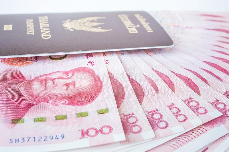Lamphun, Thailand - December 20, 2015 Yuan banknotes from China'. S currency and thailand passport ready to travel . Chinese banknotes stock photo