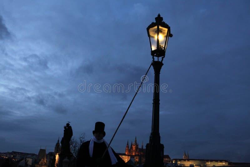 Lamplighter steekt een licht van het straatgas in Charles Bridge in P aan stock afbeelding