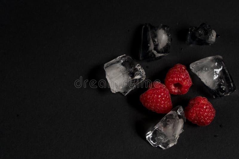 Lamponi e bei pezzi di ghiaccio su un fondo nero immagini stock libere da diritti