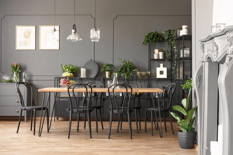 Lampor ovanför trätabell- och svartstolar i grå matsal in arkivbilder