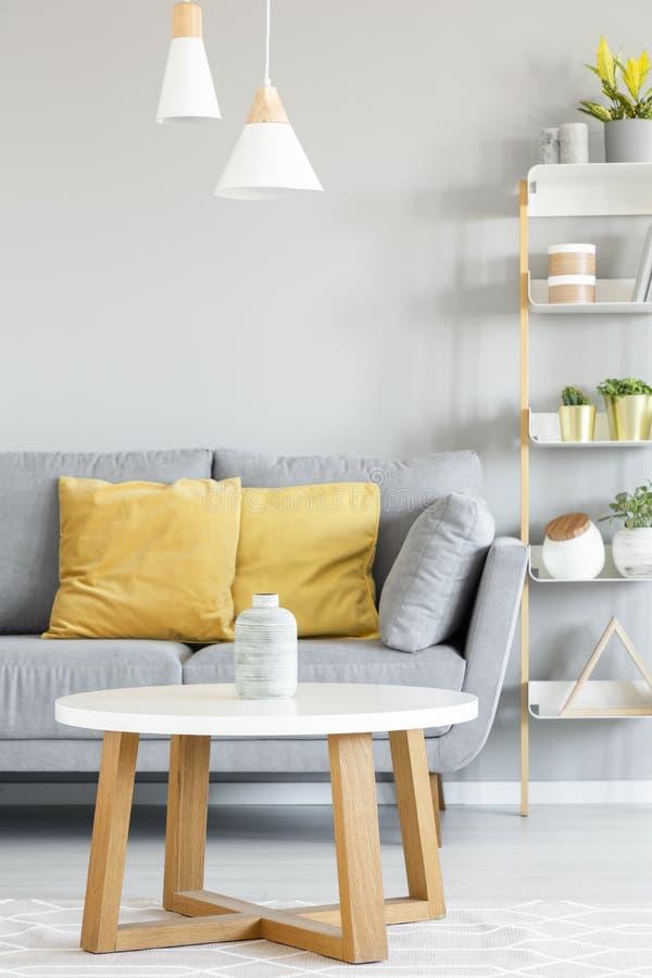 Lampor ovanför trätabellen framme av den gråa soffan med gul pillo royaltyfri foto