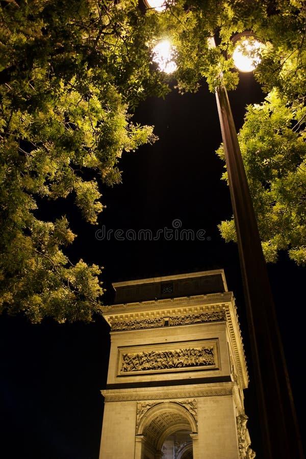 Lampost в деревьях вечером с Триумфальной Аркой осветило Париж, Францию стоковые фотографии rf