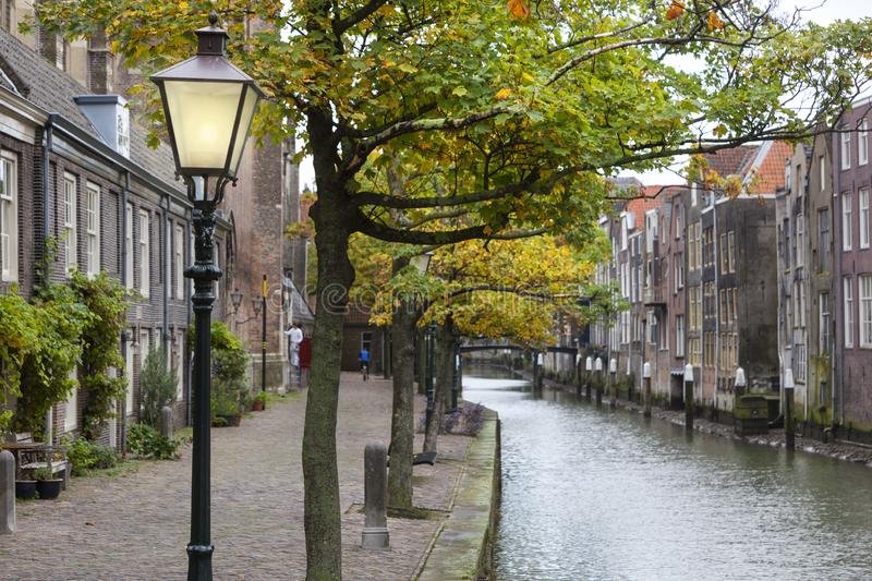Lamppost and Canal houses in Dordrecht in the Netherlands. Unsharp historic canal houses along the Voorstraathaven and a selective focus on a lamppost in stock photography