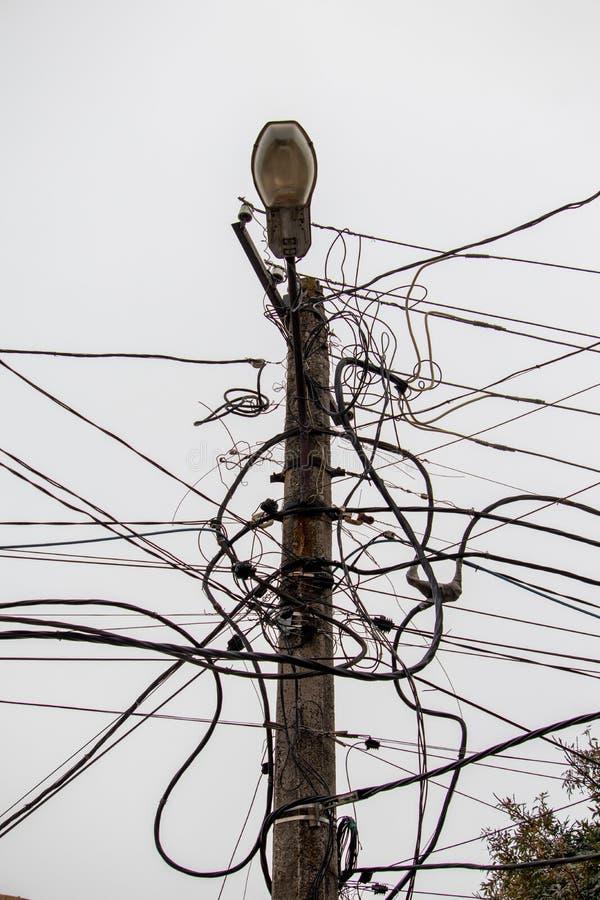 Lamppost com paus de fios fixados aleatoriamente e emaranhados imagens de stock