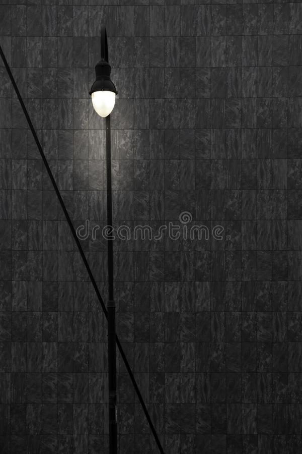Lamppost in front of a grey wall royalty free stock photo
