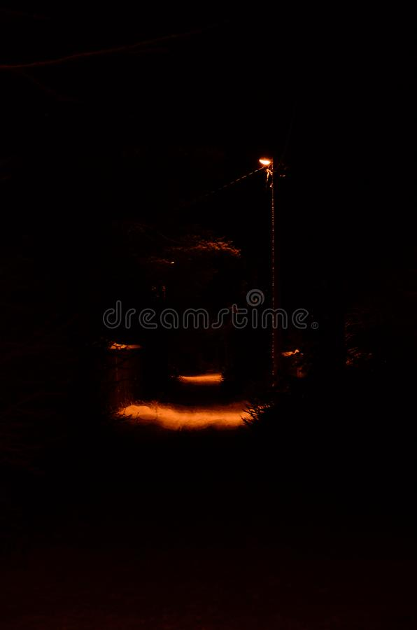 The lamppost illuminates a small spot on the dark footpath in the night stock images