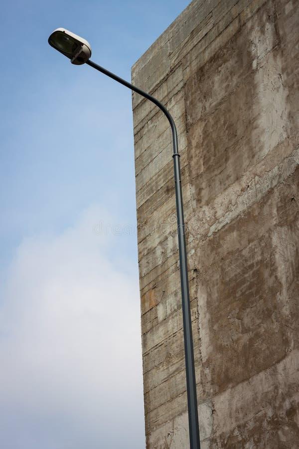 Lamppost med en betongvägg och en sky på bakgrund royaltyfri fotografi