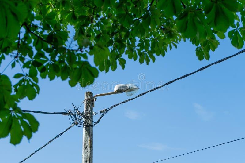 Lamppost met vele kabels die in verschillende richtingen lopen stock afbeeldingen