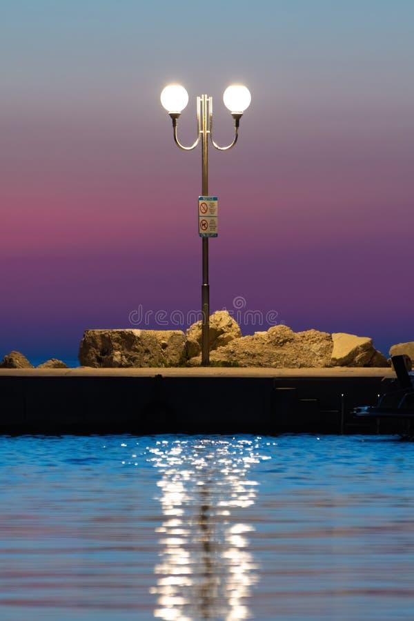 Lamppost na molu po sunet z magicznie barwionym niebem w tle obraz stock